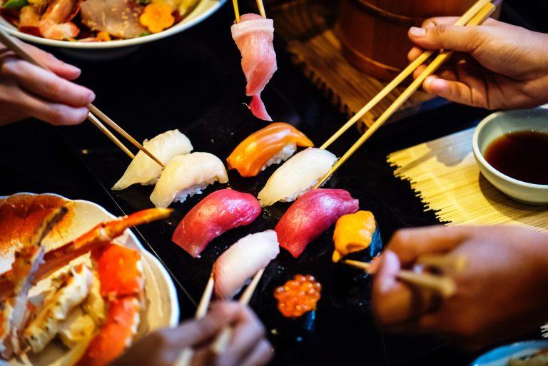 Foto de cinco pessoas segurando hashis e pegando diferentes sushis em um prato, que está em cima de uma mesa. Nesta mesma mesa, nota-se a presença de outros pratos, além de um porta shoyu.