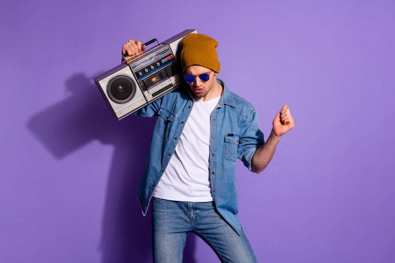 Imagem de um rapaz segurando uma boombox.