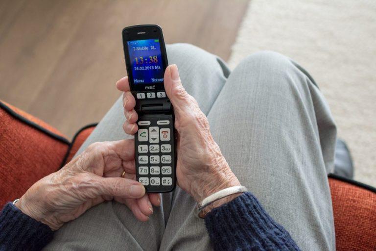 Idosa sentada, com celular flip aberto nas mãos.