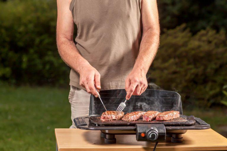 Homem preparando carne em churrasqueira elétrica.