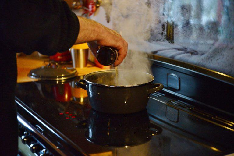 Homem cozinhando em um cooktop.