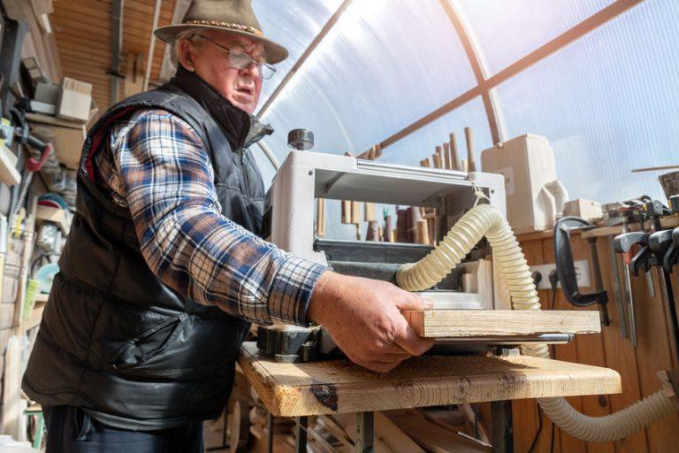 Imagem mostra um senhor colocando uma tábua em uma desengrossadeira.