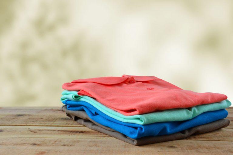 Foto de quatro camisas polo, cada uma de uma cor, em cima de uma superfície de madeira.
