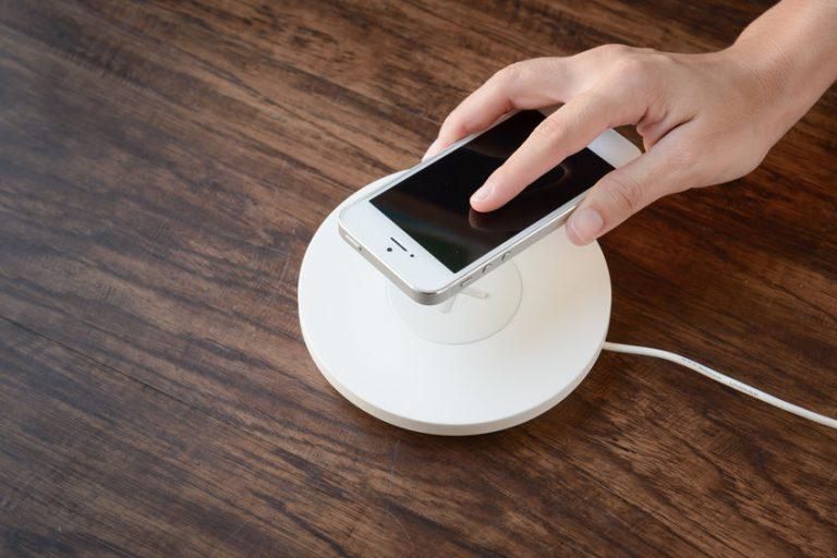 Foto da mão de uma pessoa colocando um iPhone branco em cima de um carregador por indução da mesma cor.