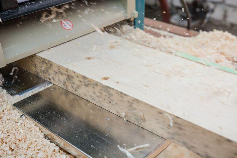 Imagem mostra uma peça de madeira em uma desengrossadeira.