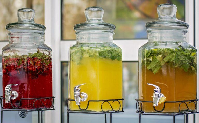Imagem mostra três refresqueiras lado a lado com sucos diferentes.