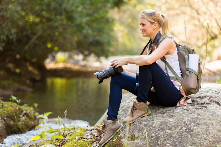 Foto de uma mulher sentadas em pedras, fotografando algo, e trajando roupa preta e confortável, com uma mochila nas costas.