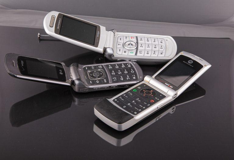 Três celulares flip abertos.