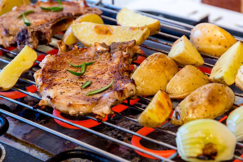 Grelha de churrasqueira elétrica em close com bife, batatas e cebolas.