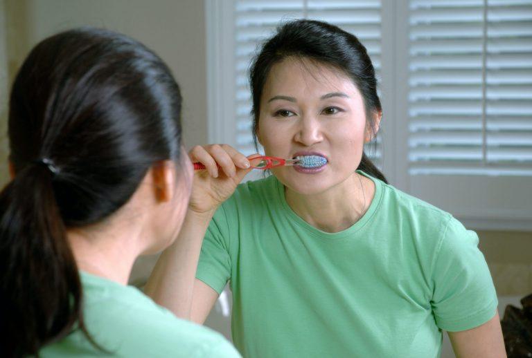 Mulher escovando os dentes.