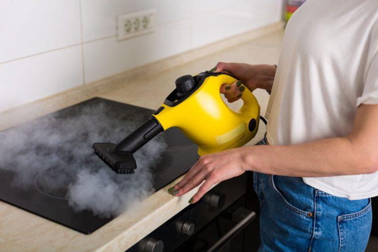 Imagem de uma mulher utilizando um vaporizador na limpeza do fogão.