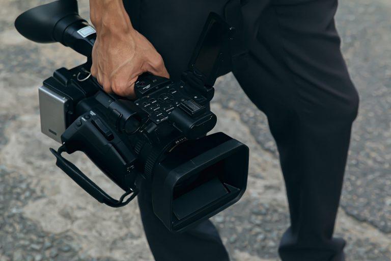 Homem segurando uma filmadora pela alça de transporte.