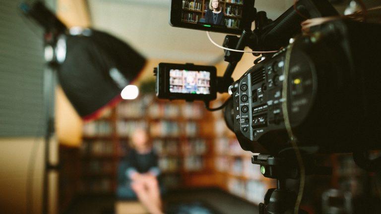 Filmadora filmando uma mulher sentada na sala.