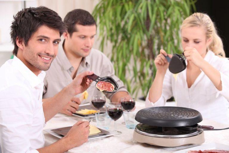 Imagem de um grupo de amigos comendo raclete.