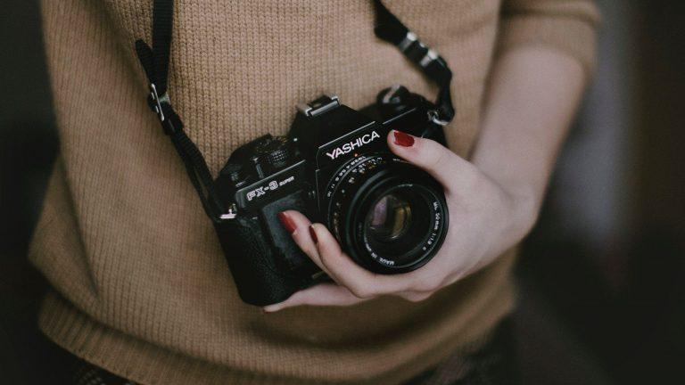 Mulher com câmera mirrorless pendurada no pescoço.
