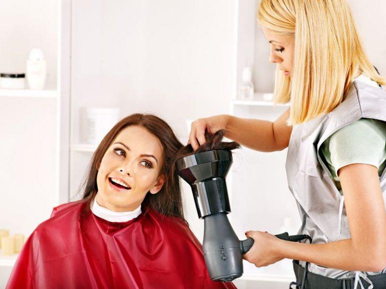 Imagem de uma cabelereira secando o cabelo da cliente com um secador com difusor.