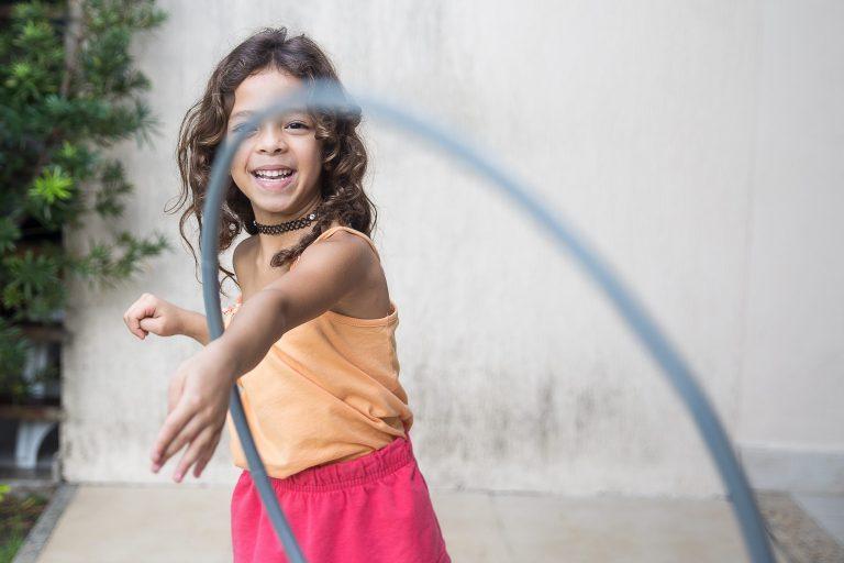 Imagem de uma criança brincando com bambolê.