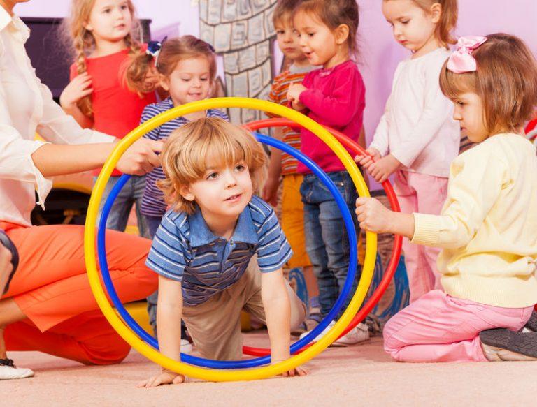 Imagem de crianças brincando com bambolês.