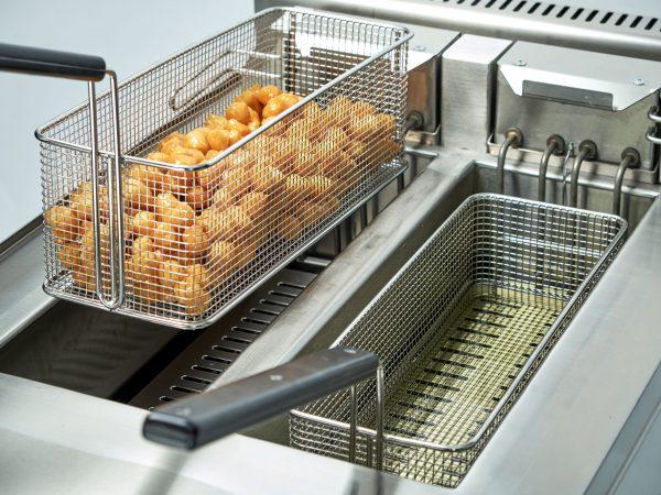 Imagem de uma fritadeira industrial dupla com salgadinho em um cesto