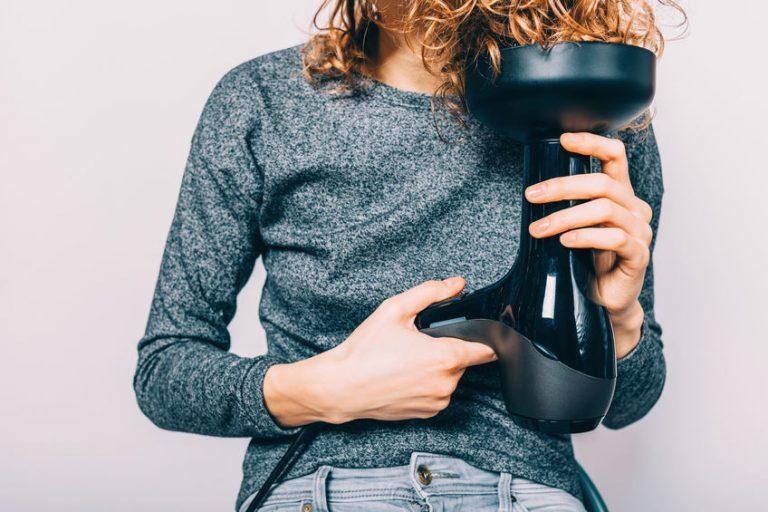 Imagem de uma mulher utilizando um secador com difusor.