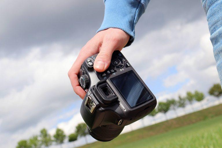 Mão segurando uma câmera fotográfica.