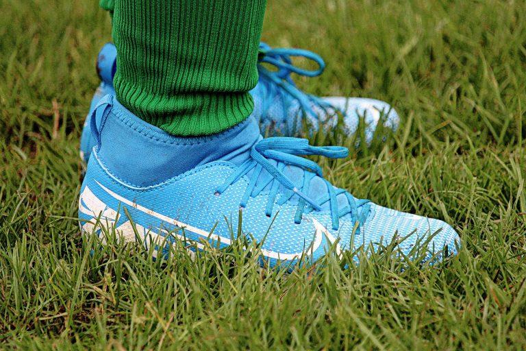 Imagem mostra uma pessoa usando chuteira botinha azul em um campo.
