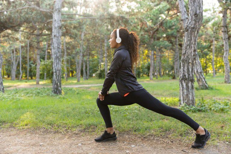 Mulher se alongando em parque para fazer exercício