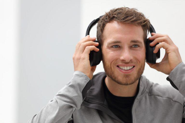 Homem sorrindo colocando um headphone sem fio