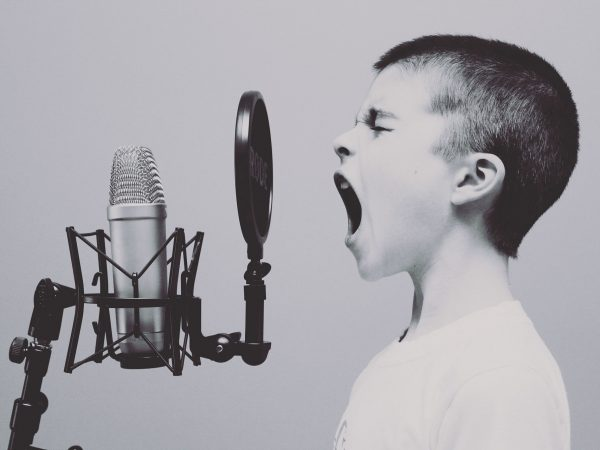 Menino cantando no microfone.