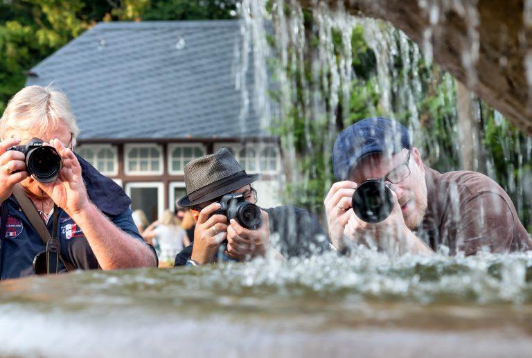 Três fotógrafos tirando fotos atrás de uma fonte de água.