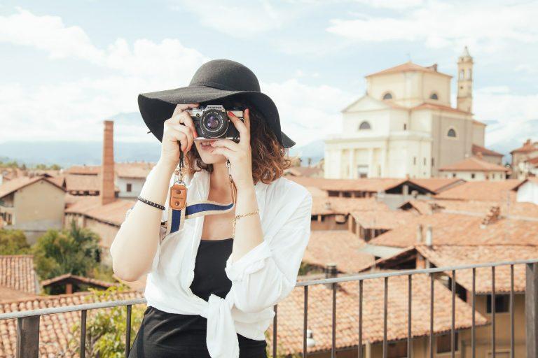 Mulher de chapéu tirando foto com uma câmera mirrorless.