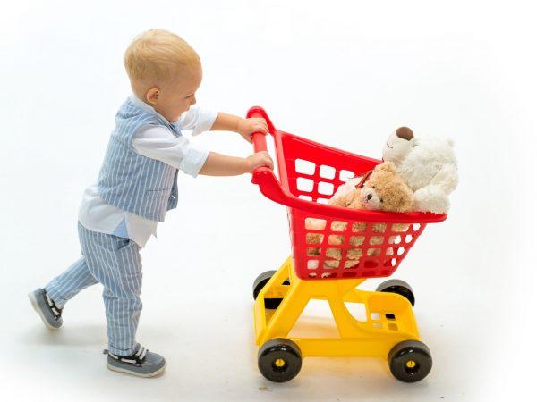 Na foto um menino pequeno empurrando um carrinho de compras de brinquedo.