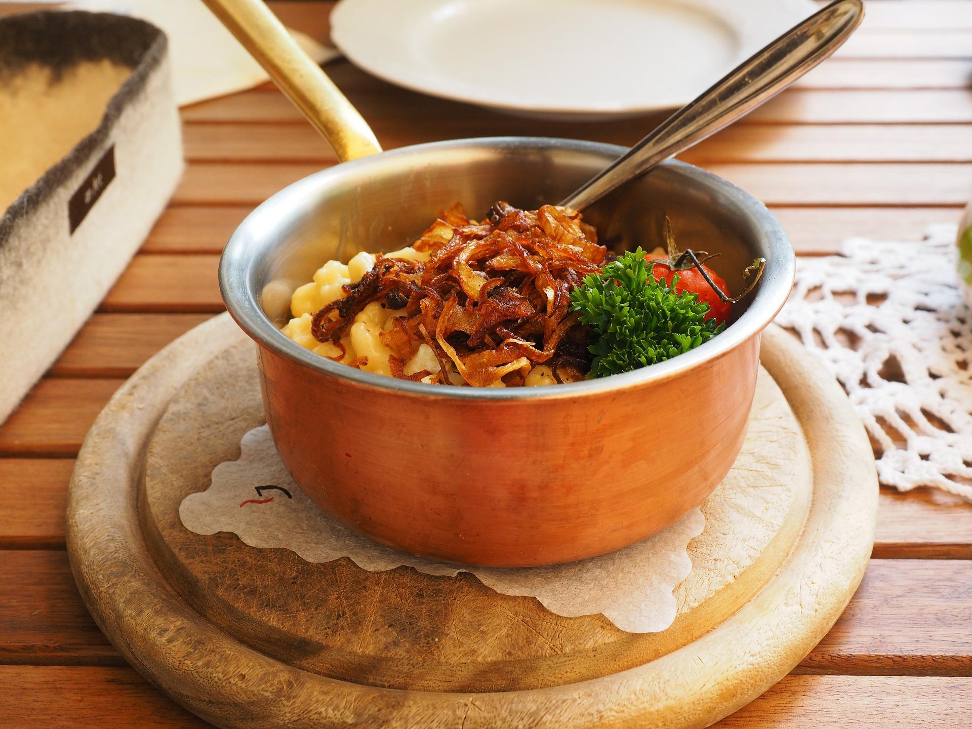 Panela com alimentos prontos apoiada sobre descanso em madeira