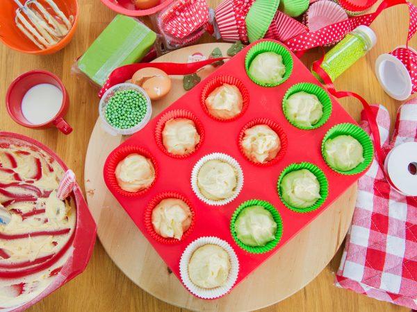 Forma de silicone para muffins vermelha repleta de massa ao lado de ingredientes