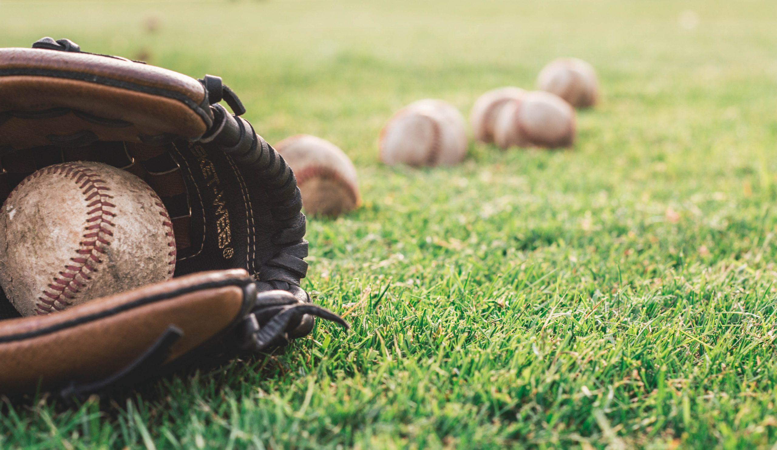 Imagem mostra uma luva de baseball abrigando uma bola sob um gramado. Ao fundo, outras cinco bolas soltas no gramado, desfocadas.