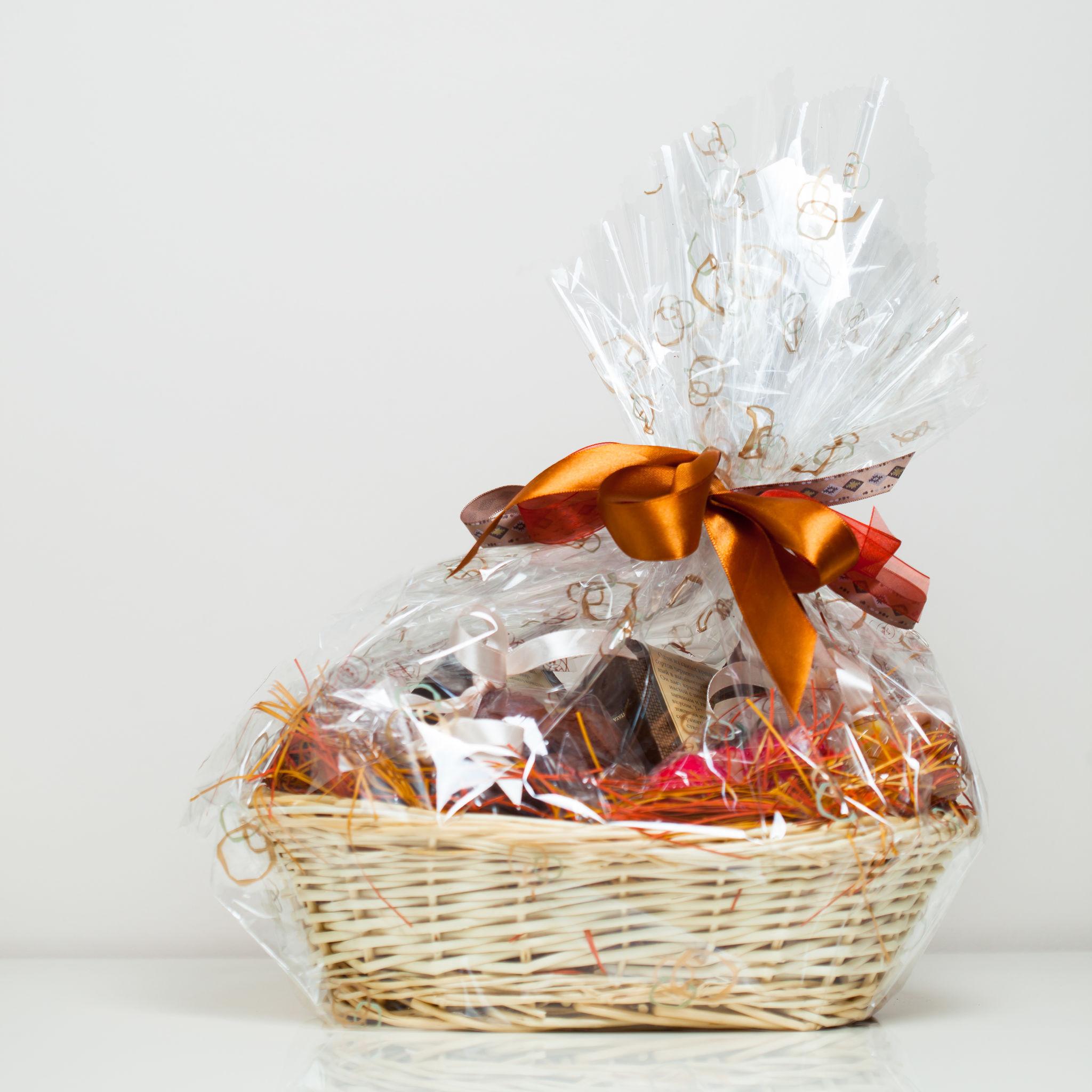 Na foto uma cesta com produtos para presente embalada com papel celofane e um laço marrom claro metalizado.