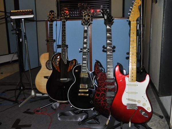 Imagem de violões e guitarras alinhados e apoiados em suportes de piso