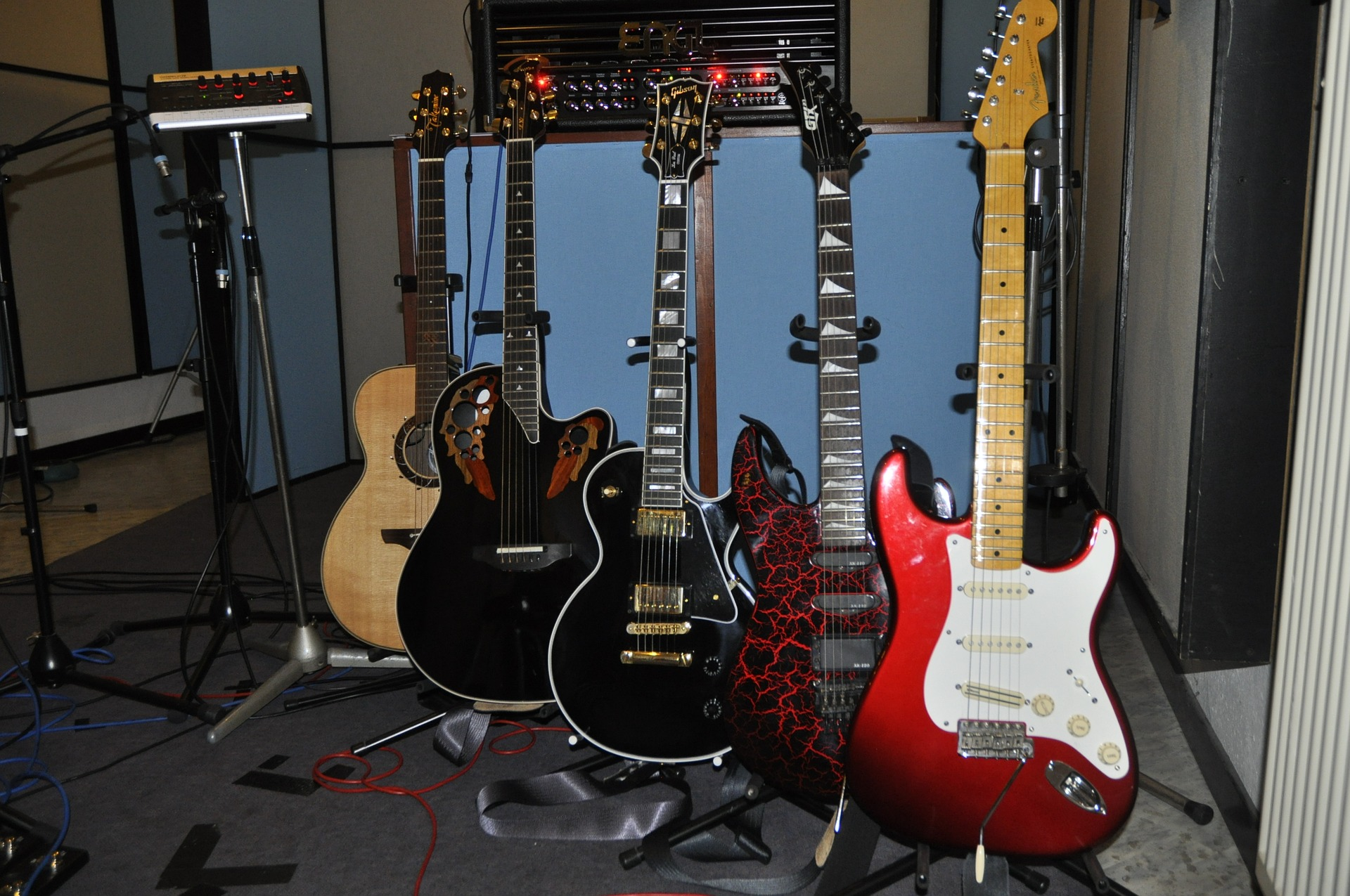 Image of guitars and guitars aligned and supported on floor stands