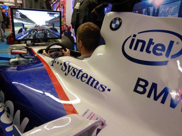 Imagem de pessoa jogando em simulador de Fórmula 1 com volante