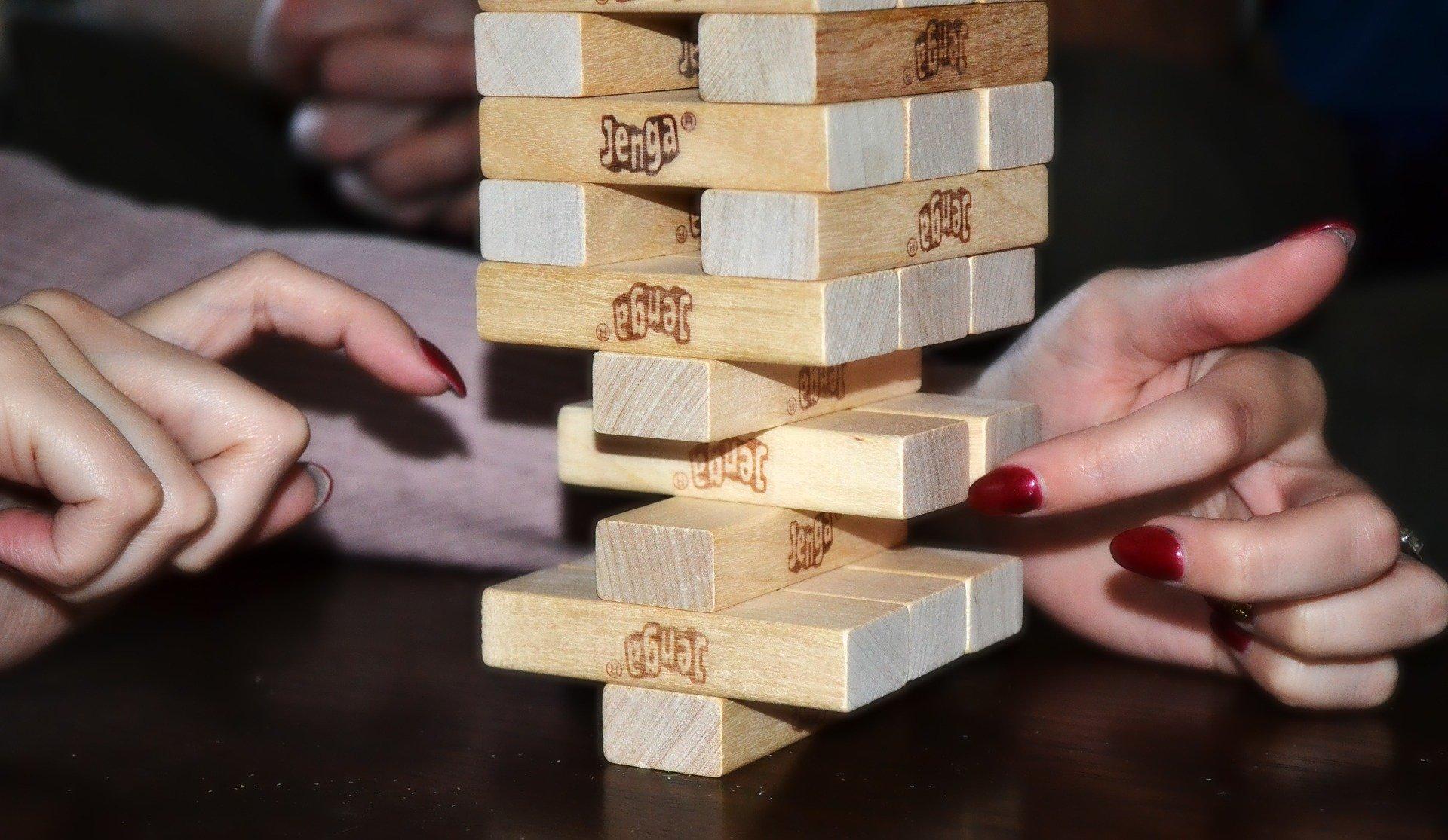 Duas mãos femininas mexendo em uma torre com blocos de Jenga.