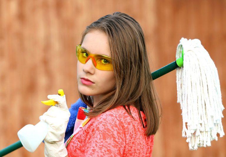 Uma mulher com luvas que carrega um esfregão, uma toalha, um squeeze e óculos de proteção colorido.