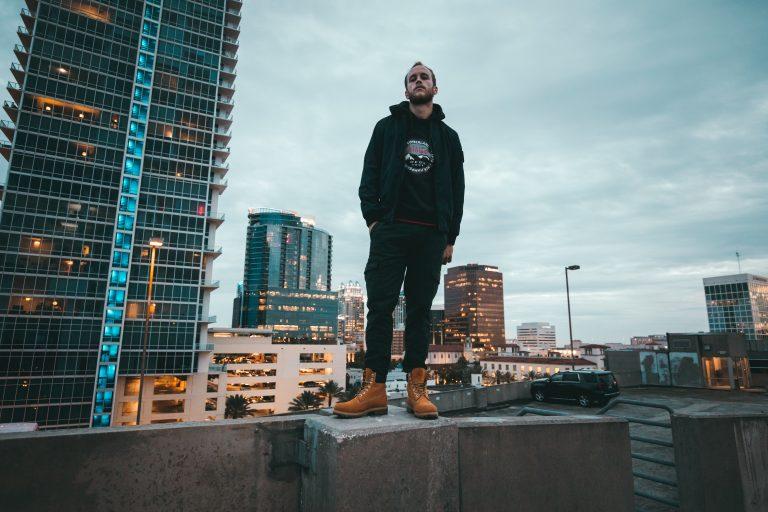 Imagem mostra um homem, com uma bota Timberland, posando no topo de um prédio.