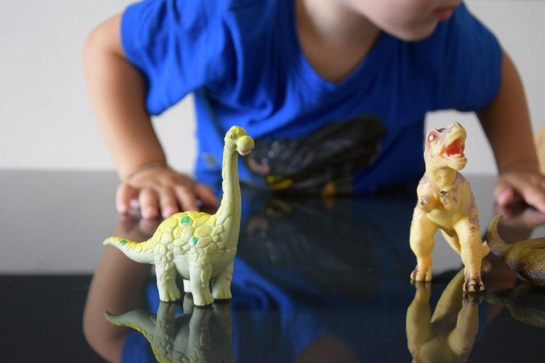 Imagem das mãos de uma criança brincando com bonecos de dinossauros
