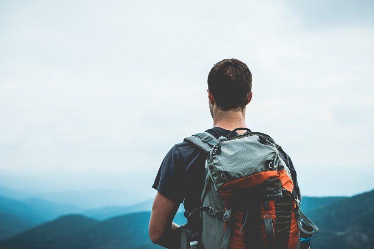 Um homem de camiseta com uma mochila em cima de uma montanha olhando para os topos de outras montanhas.