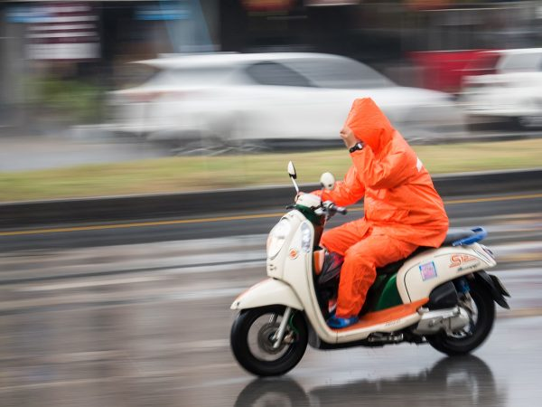 Uma pessoa com capa de chuva de motoqueiro laranja pilotando moto branca.