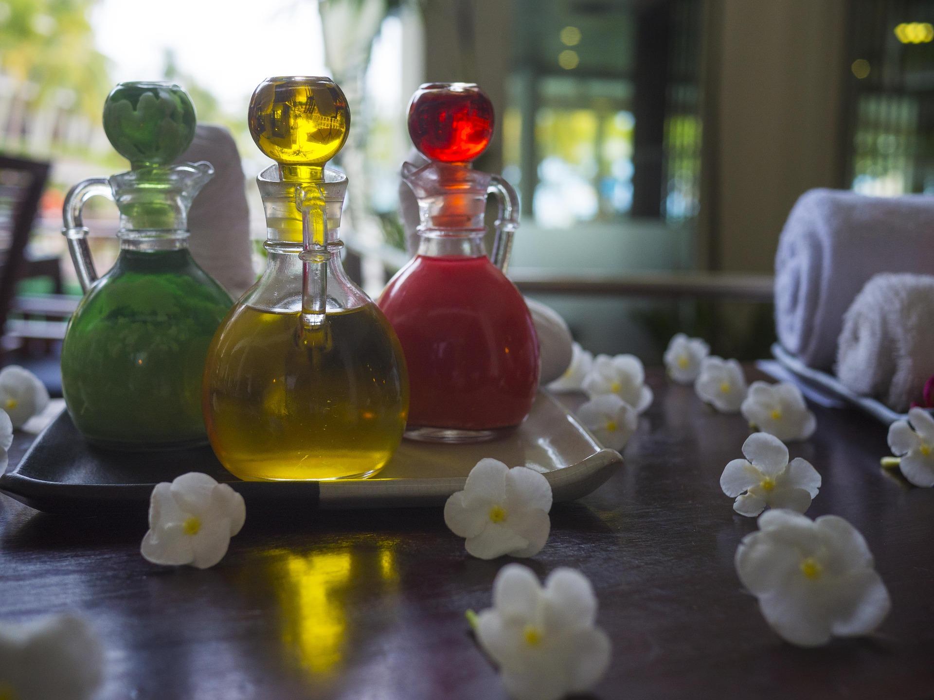 Imagem de frascos com diferentes óleos corporais em bancada de spa decorada com flores