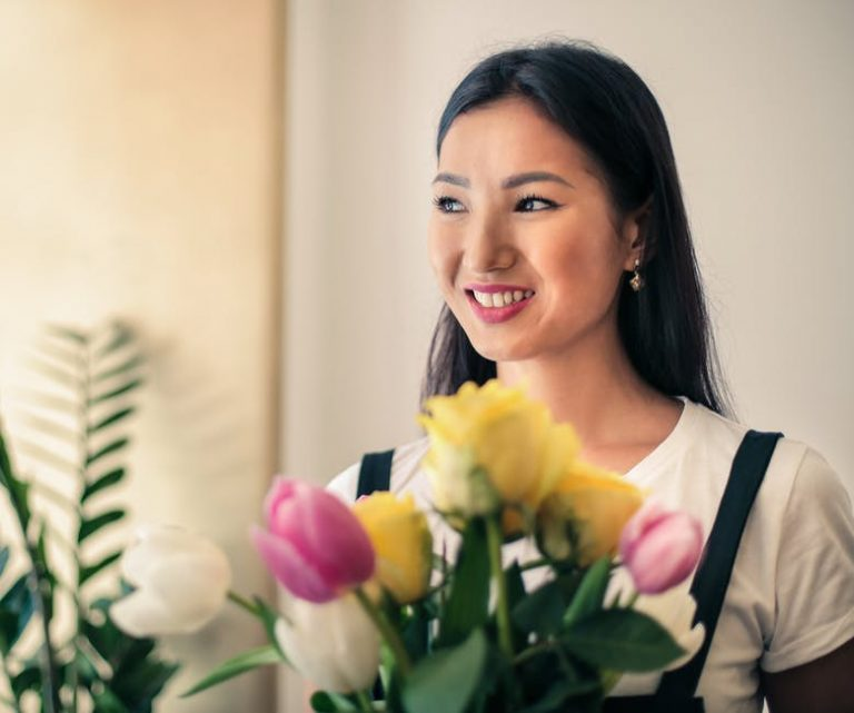 Na foto uma mulher sorrindo com um ramalhete de flores amarelas, rosas e brancas na sua frente.