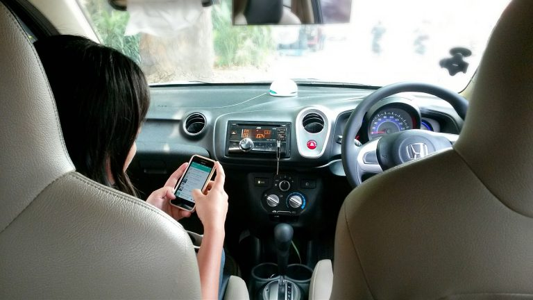 Uma mulher mexendo em um celular sentada no banco do passageiro frontal de um carro britânico.