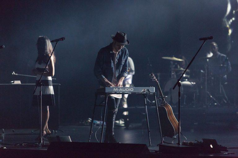 No palco, banda toca e tecladista tem violão apoiado em suporte ao seu lado