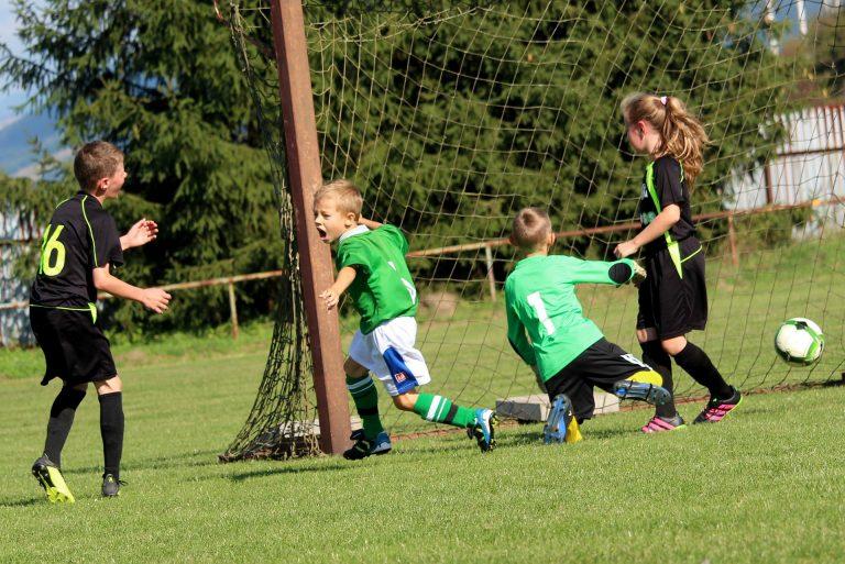 Imagem mostra uma pelada entre garotos, no momento e que um dos pequenos jogadores marca o gol. A bola vai entrando na rede enquanto ele comemora, e os três adversários da imagem, lamentam.